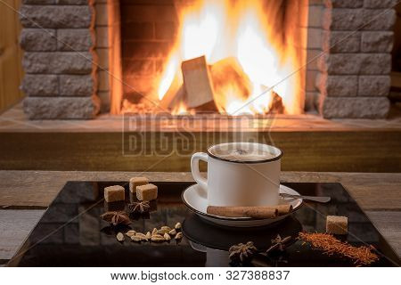 Cozy Scene Before Fireplace With A Cup Of Masala Chai Tea With Spices, In Country House, Winter Vaca