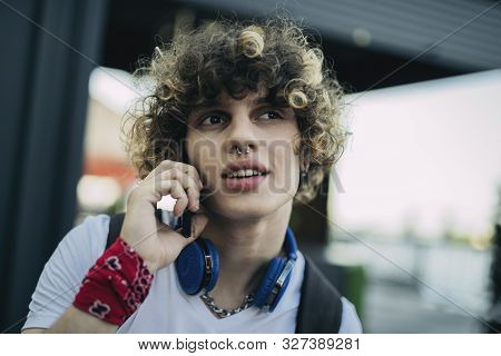 Carefree Boy Talking On Cell Phone Outdoors Stock Photo