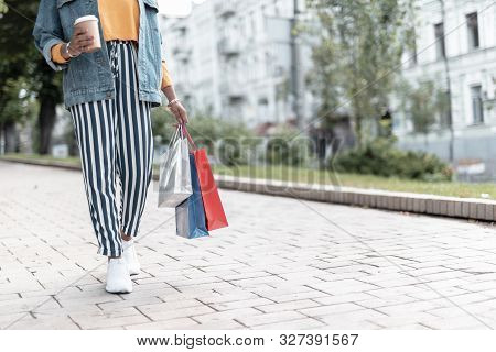 Trendy Girl With Hot Drink Going Shopping Stock Photo