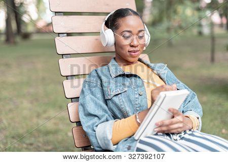 Merry Girl With Sketchbook And Earphones In Park Stock Photo