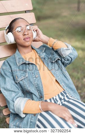 Happy Woman Relaxing With Music In Park Stock Photo