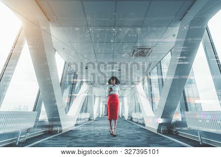 African-american Woman Entrepreneur Is Standing Indoors Of A Long Bright Futuristic Passageway Of A