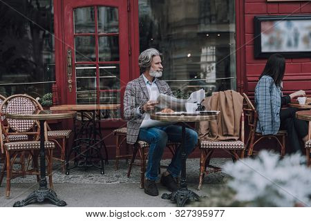 Cozy Cafe Terrace And Interesting Newspaper Stock Photo