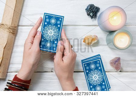 Tarot Cards In Fortune Teller Hand On White Wooden Table Background. Future Reading.