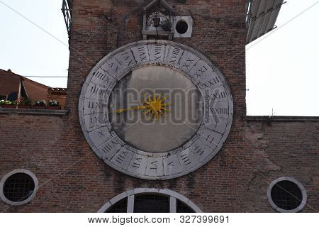 Venice, Italy, 04.19.2019: An Ancient Clock With One Hand, Divided Into 24 Hours On The Church Of Sa