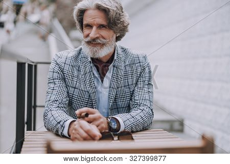 Cheerful Mature Man At The Cafe Table Smiling Stock Photo