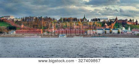 Nizhny Novgorod Kremlin and city buildings at sunset with the Volga River. Panorama.