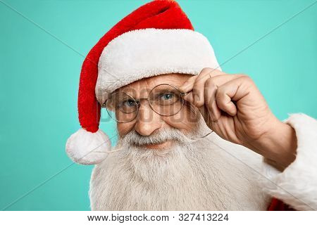 Happy Authentic Santa Claus In Red Hat And Eyeglasses Posing On Camera On Blue Background. Saint Nic