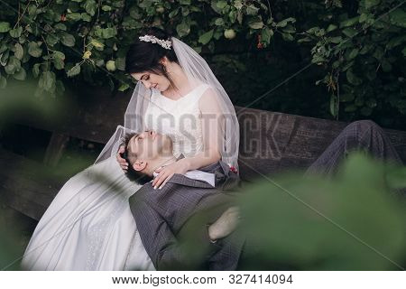 The Bride Sits In The Arms Of Her Fiance.happy Newlyweds Enjoy A Walk In The Park.