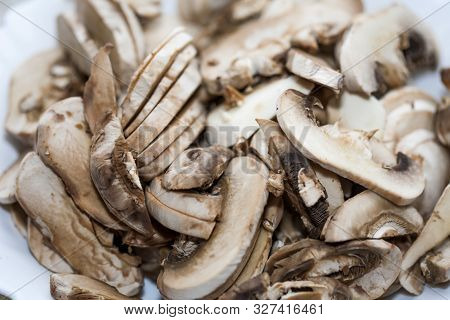 Chopped Mushrooms On A Chopping Board. Mushrooms Chopped And Lined On A Brown Board.
