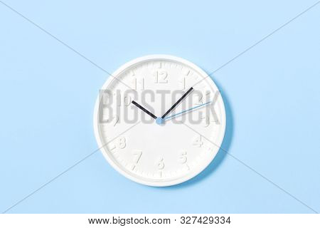 White Big Analogue Plain Wall Clock On Trendy Pastel Blue Background. Ten Oclock. Close Up With Copy