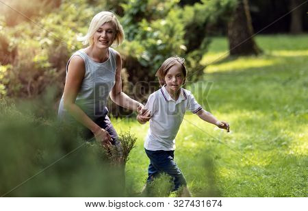 Athletic Young Mother And Her Special Son Wandering Through A Summer Park