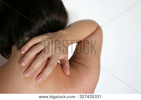 Neck Pain, Woman Clutched By Hand Her Shoulder, Back View. Concept Of The Spine Injury, Clavicle And
