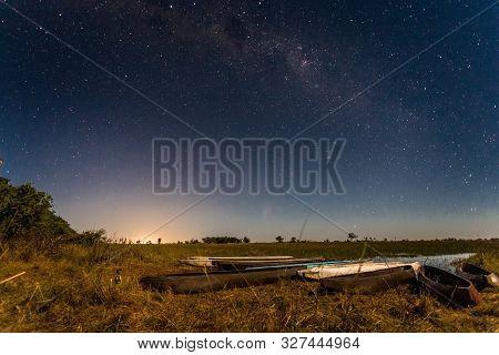 Botswanian Local Mokoro Boats Under The Starlight Sky, On The Shore Of Delta Okavango River, Botswan