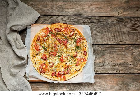 Baked Round Pizza With Smoked Sausages, Mushrooms, Tomatoes, Cheese And Arugula Leaves, Food Is Cut
