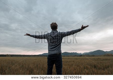View From Behind Of A Young Man Standing In Autumn Meadow Under Cloudy Evening Sky With His Arms Wid
