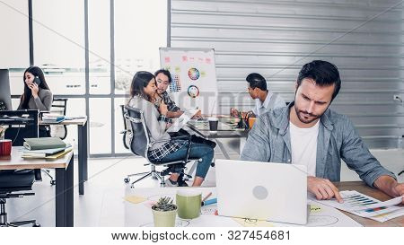 Creative Designer Director Checking Work On Laptop While Team Is In Casual Meeting At Background In