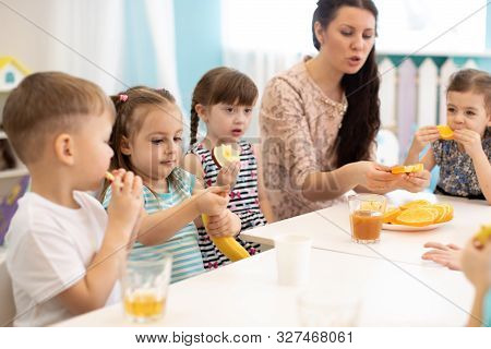 Children And Carer Together Eat Fruit As A Snack In The Kindergarten, School Or Daycare