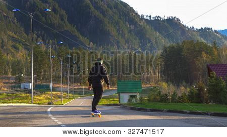 A Young Man In Blue Sneakers On A Long Board On An Asphalted Road In A National Park.