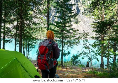 A Girl With A Backpack In A Knitted Hat Stands By A Green Tent And Looks At The Amazing Lake.