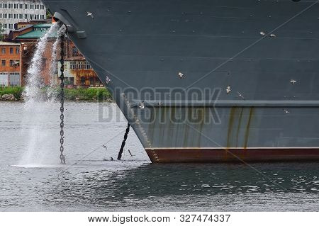 Big Ship Hauling Up The Anchor. Small Seagulls On The Huge Bow Background.
