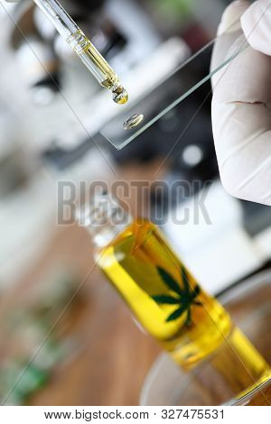 Focus On Pharmacist Hand Dripping Drops Of Cannabinoid Oil With Pipette On Test Glass. Testing Of Cb