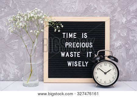 Time Is Precious Waste It Wisely. Motivational Quote On Letterboard, Black Alarm Clock, Flower In Va