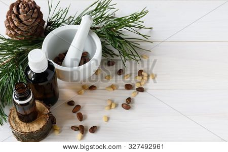 Cedar Oil, Branches And Cedar Cone On White. Copy Space. Beauty And Healthy Concept.energizing Facia