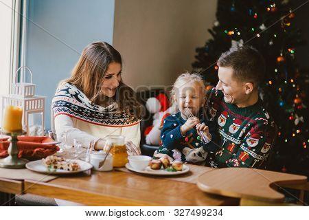 Happy Family Having Holiday Breakfast On Christmas Morning.