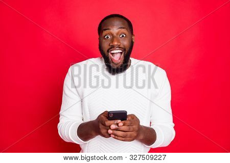 Photo Of Funny Dark Skin Man Holding Telephone Hands Reading New X-mas Comments In Blog Wear White K