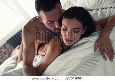 Passionate Young Couple Having Sex In Bed At Home