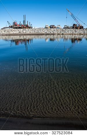 The Clear Water And Dark Goldbearing Sands Of The Bering Sea In Nome Alaska.