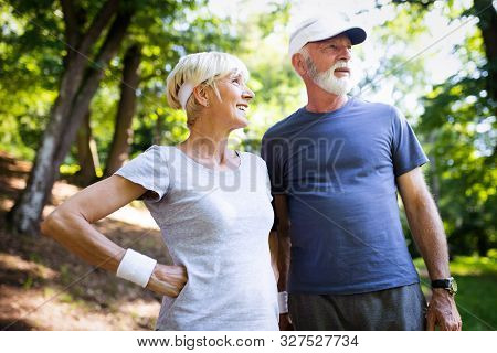 Active Mature Couple Running In The Park For Helathy Life