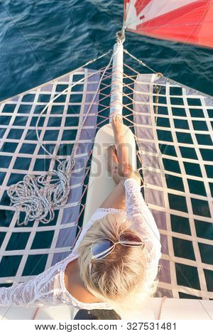 Beautiful young fair-haired woman dressed in a swimsuit and white pareo sitting on a yacht bow during sea journey. Top view. Selective focus on hair. Sea trip. poster