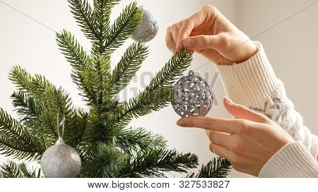 Decorate The Christmas Tree With Christmas Toy. Closeup Image Of Woman In Sweater Decorating Christm