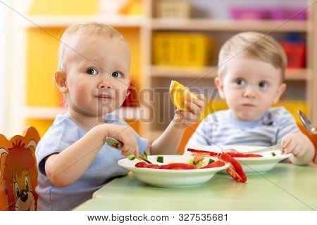Cute Children Eat Healthy Food In Nursery Or Creche