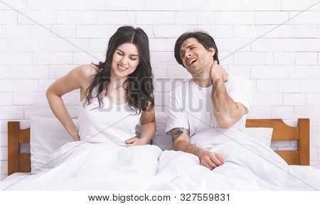 Uncomfortable Mattress. Young Sad Couple Waking Up, Suffering From Back And Neck Ache After Bad Nigh