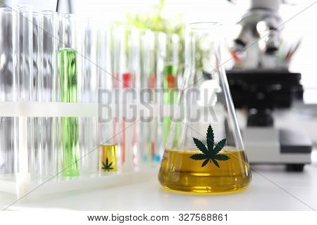 Test Tube With Yellow Cbd Oil In Chemisrtry Lab Research Background Closeup. Medical Marijuana Conce