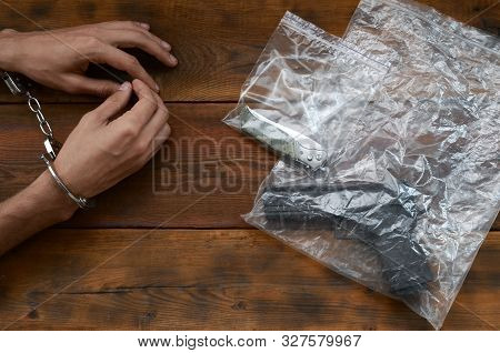 Handcuffed Hands Of Criminal Suspect On Wooden Table And Handgun With Jackknife In Transparent Plast