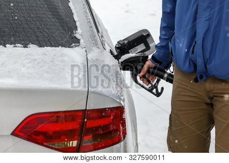 Man Filling Fuel To His Diesel Car At Gas Station In Winter. Detail On Snow Covered Tank Cover And P