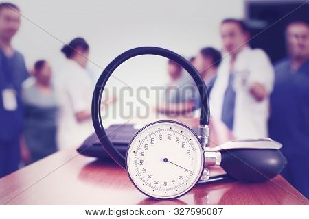 Device For Measuring Blood Pressure On A Table In A Staff Room Against A Background Of A Group Of Wo