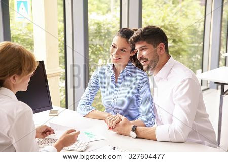 Investment Advisor Businesswoman Giving Savings Ideas To Young Couple