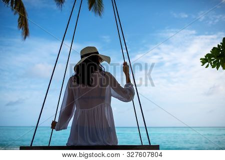 Young Beautiful Woman Relaxing In Swing Hanging On Coconut Palm At Exotic Beach.blue Sea And White S