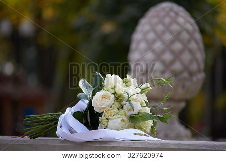 White Bouquet Of Alstroemeria With A White Ribbon On A Blurred Background Of A Balustrade In The Par