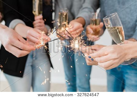 Hands of young multicultural friends holding burning bengal lights and flutes of champagne at new year party