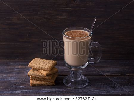 Spicy Warming Tea With Milk In A Glass Cup With Cinnamon, Gingerbread Cookie On A Wooden Table,  Rus
