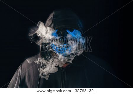 Man With Lighting Neon Glow Mask In Hood And Vape Vapour From Mask On Black Background. Halloween An