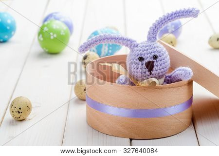 Knitted Lilac Bunny In A Gift Box, Close-up. Light Wooden Surface, Easter And Quail Eggs On The Back