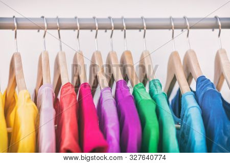Clothes hanging on clothing rack wardrobe fashion apparel selection of rainbow color t-shirts on closet hangers. Womens wear in store shopping spring cleaning concept. Summer home wardrobe.