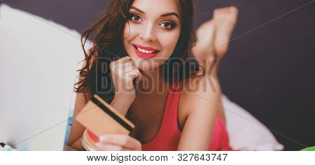 Beautiful Woman Lying On Bed With A Laptop And Credit Card